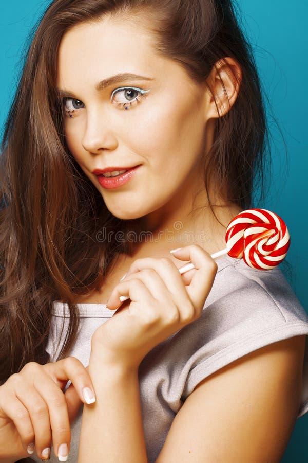 Jonge vrij donkerbruine vrouw die gelukkige vrolijk op blauwe achtergrond met suikergoed stellen, het concept van levensstijlmens royalty-vrije stock afbeelding