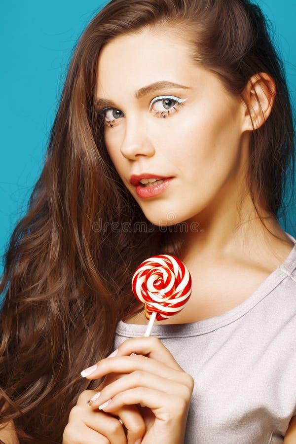 Jonge vrij donkerbruine vrouw die gelukkige vrolijk op blauwe achtergrond met suikergoed stellen, het concept van levensstijlmens royalty-vrije stock afbeeldingen