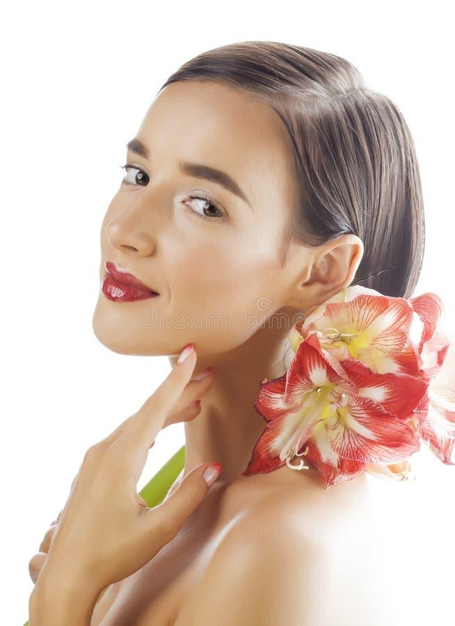 Jonge vrij donkerbruine vrouw met rode dichte die omhooggaand van de bloemamaryllis op witte achtergrond wordt geïsoleerd Buitens royalty-vrije stock foto's