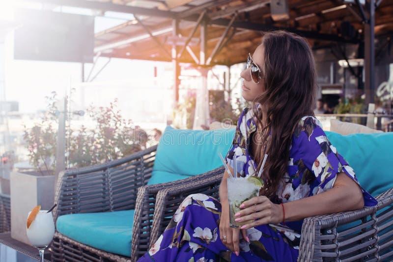 Jonge vrij donkerbruine vrouwenzitting bij koffie buiten met cocktai stock afbeelding