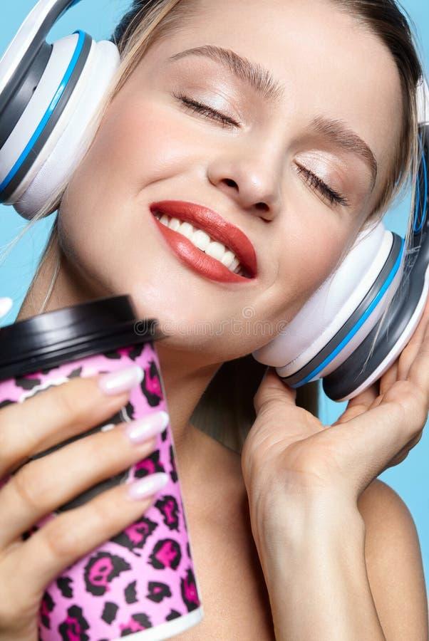 Jonge vrij gelukkige vrouw het drinken koffie en het luisteren aan muziek in hoofdtelefoons royalty-vrije stock foto's