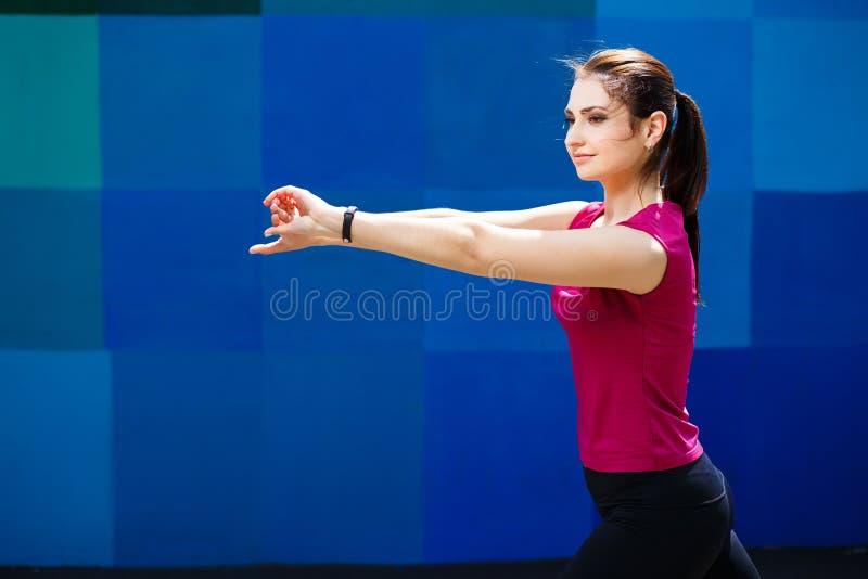 Jonge vrij geschikte vrouw die bij het atletische gebied uitwerken royalty-vrije stock fotografie