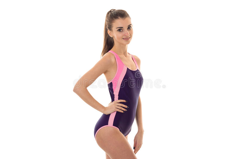 Jonge vrij slanke donkerbruine dame in lichaamszwempak met hand bij haar heup glimlachen geïsoleerd op witte achtergrond stock foto's