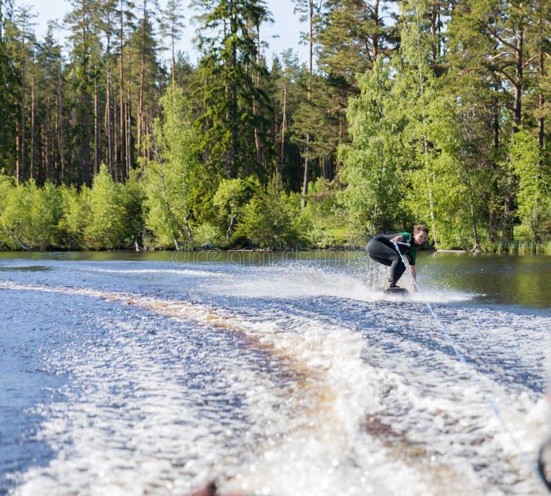 Jonge vrij slanke donkerbruine vrouw in wetsuit die wakeboard op golf van motorboot berijden royalty-vrije stock fotografie