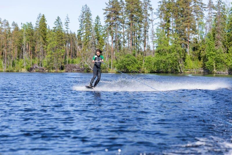 Jonge vrij slanke donkerbruine vrouw in wetsuit die wakeboard op golf van motorboot berijden stock foto