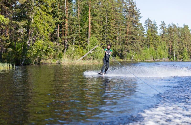 Jonge vrij slanke donkerbruine vrouw in wetsuit die wakeboard op golf van motorboot berijden royalty-vrije stock afbeeldingen