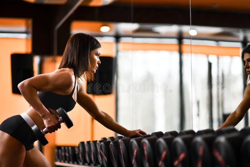 Jonge vrij slanke vrouw in de domoren van de sportkledingsgreep in gymnastiekbinnenland royalty-vrije stock afbeeldingen