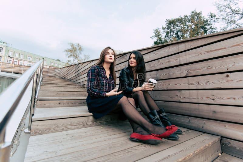 Jonge vrij twee vrouwelijke hipsters die aan elkaar spreken terwijl het zitten van op houten treden in de verse lucht, royalty-vrije stock afbeeldingen