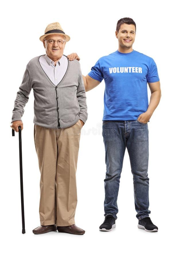 Jonge vrijwilliger die een bejaarde met een riet helpen royalty-vrije stock fotografie