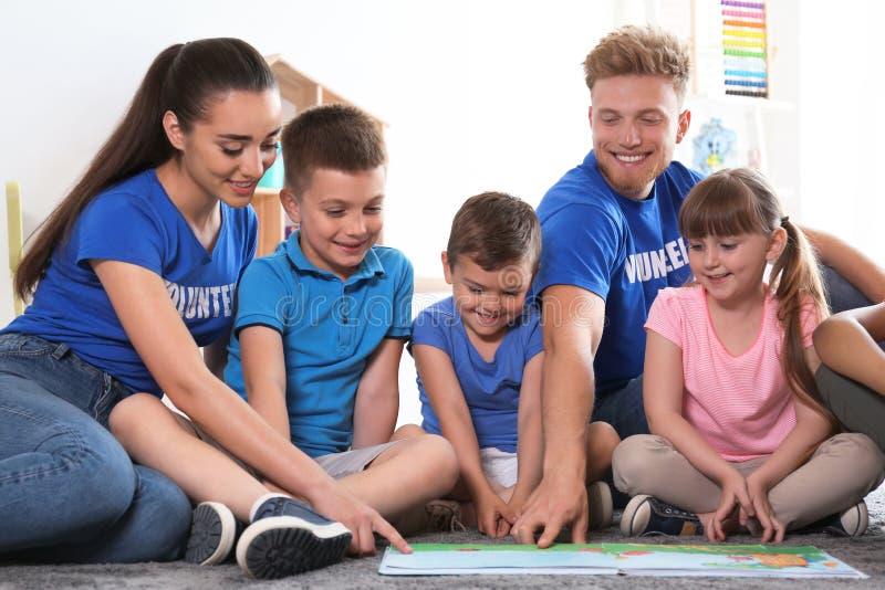 Jonge vrijwilligers die boek met kinderen op vloer lezen royalty-vrije stock afbeeldingen