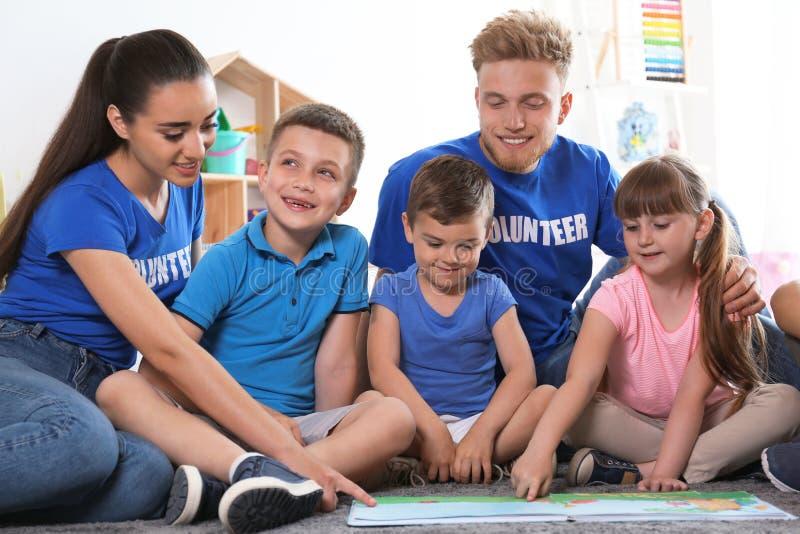 Jonge vrijwilligers die boek met kinderen op vloer lezen stock afbeeldingen