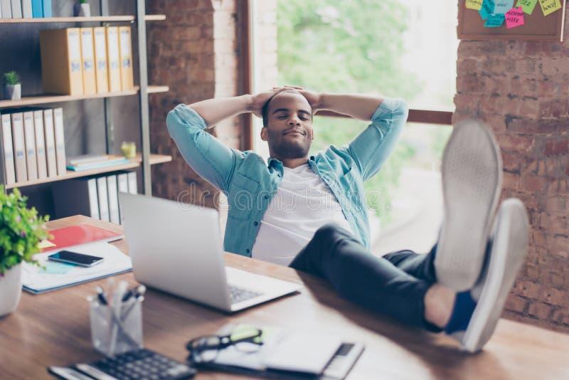 Jonge vrolijke afro freelancer rust op het werk, met voeten bovenop het bureau, met gesloten ogen, het glimlachen, het dromen royalty-vrije stock afbeelding