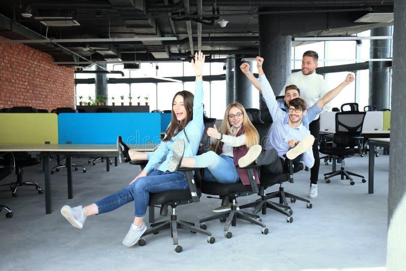 Jonge vrolijke bedrijfsmensen in slimme vrijetijdskleding die pret hebben terwijl het rennen bij bureau stoelen en het glimlachen stock fotografie