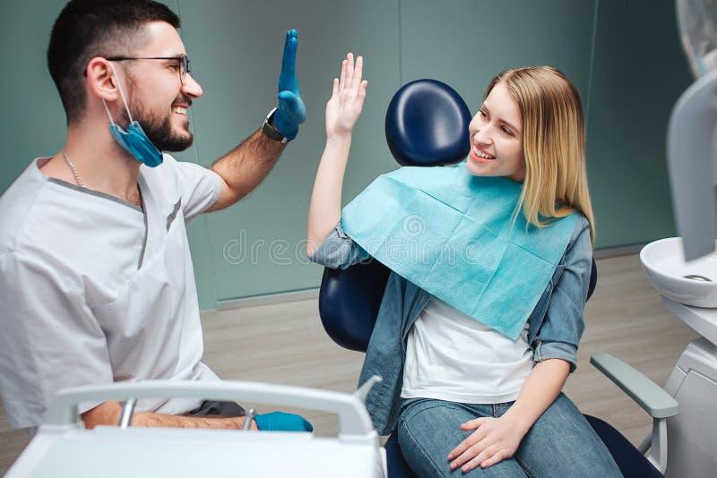 Jonge vrolijke cliënt en tandarts die hoog-vijf geven aan elkaar in tandheelkunde Zij glimlachen Het werk wordt gedaan stock foto