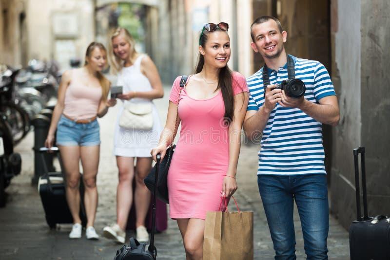 Jonge vrolijke familietoeristen die in stad fotograferen stock foto's
