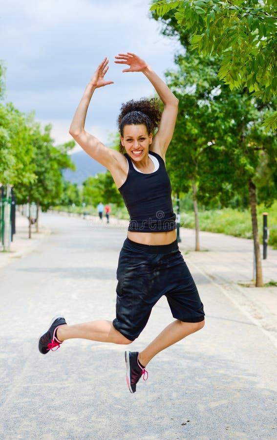 Jonge vrolijke glimlachende vrouw in sportenslijtage op stedelijke achtergrond stock fotografie
