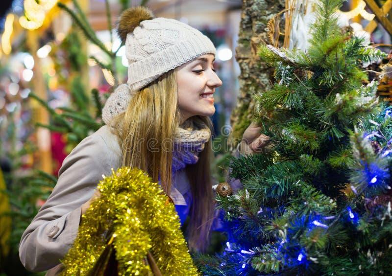 Jonge vrolijke het glimlachen vrouw het kopen Kerstmisboom bij feestelijke markt royalty-vrije stock foto