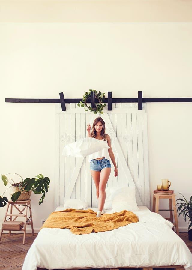 Jonge vrolijke Kaukasische vrouw die op bed springen stock fotografie