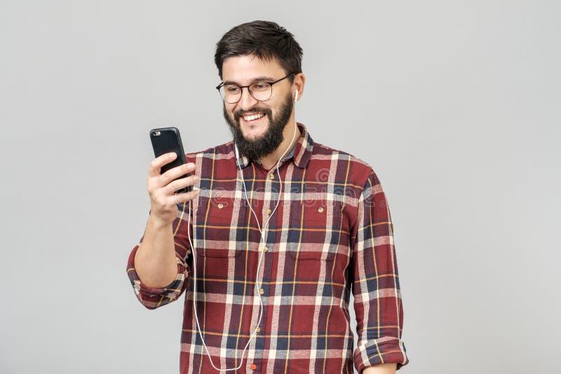 Jonge vrolijke kerel in hoofdtelefoons die holdingstelefoon glimlachen die aan muziek luisteren stock foto