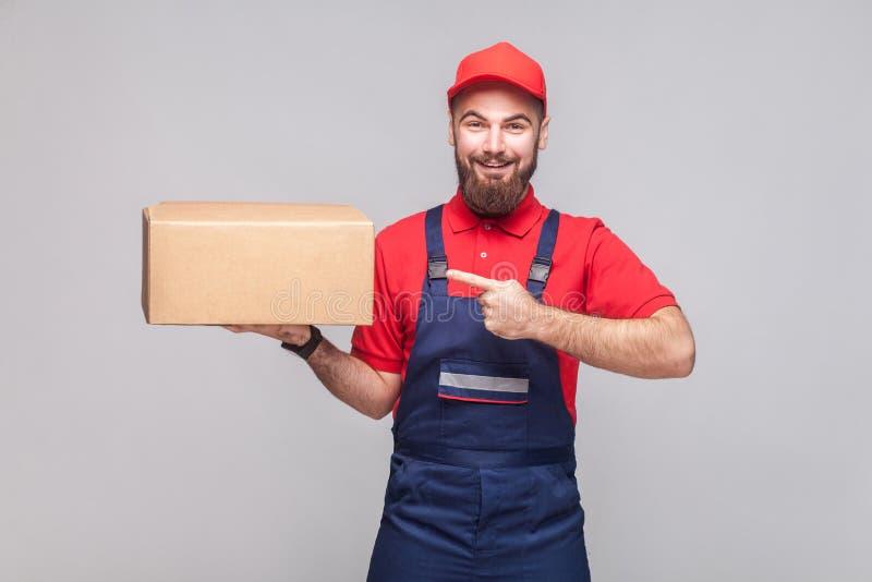 Jonge vrolijke logistische leveringsmens met baard in blauwe eenvormig stock foto's