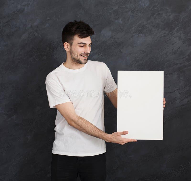 Jonge vrolijke mens met leeg Witboek stock afbeelding