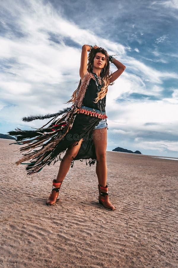Jonge vrolijke modieuze vrouw op het strand bij zonsondergang stock afbeeldingen