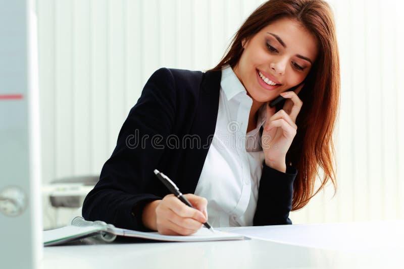 Jonge vrolijke onderneemster die op de telefoon en het schrijven nota's spreken royalty-vrije stock fotografie