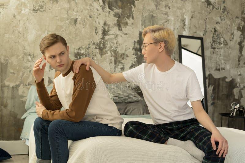 Jonge vrolijke paarruzies in bed Gedeprimeerde Europese mannelijke zitting op de rand van het bed stock afbeelding
