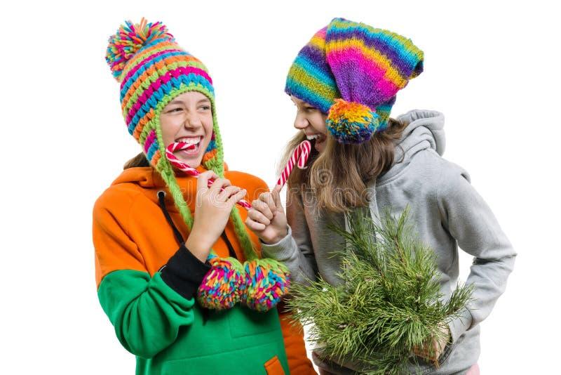 Jonge vrolijke tieners die pret met het riet van het Kerstmissuikergoed, in de winter gebreide die kappen hebben, op witte achter stock foto