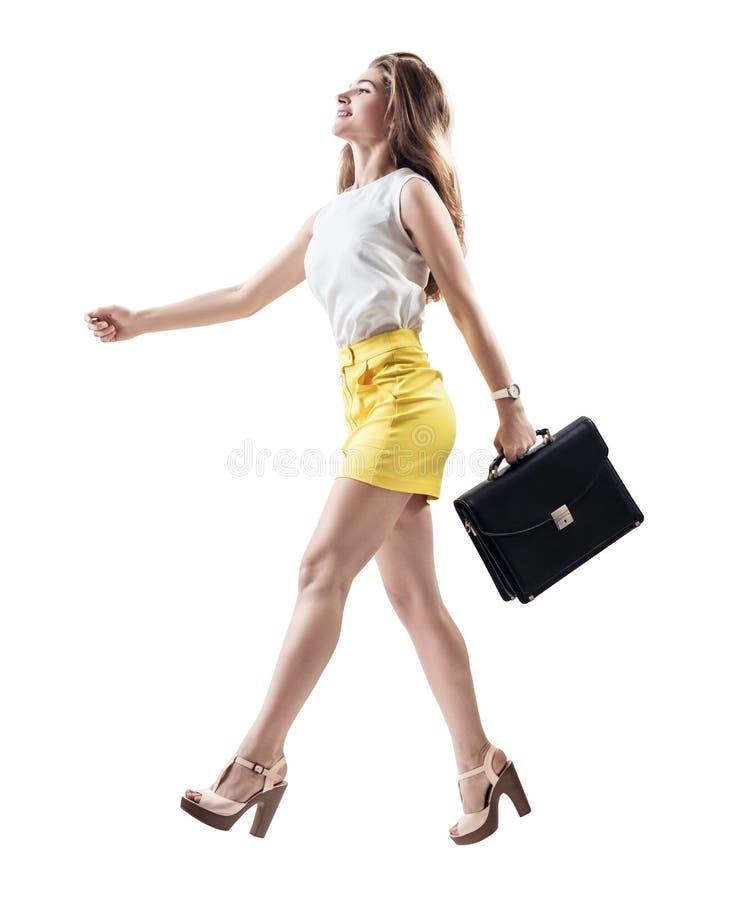 Jonge vrolijke vrouw die met aktentas lopen stock foto's