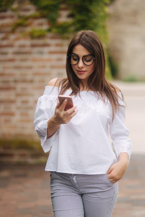 Jonge vrolijke vrouw die op grappige video op slimme telefoon letten terwijl in openlucht het rusten royalty-vrije stock foto