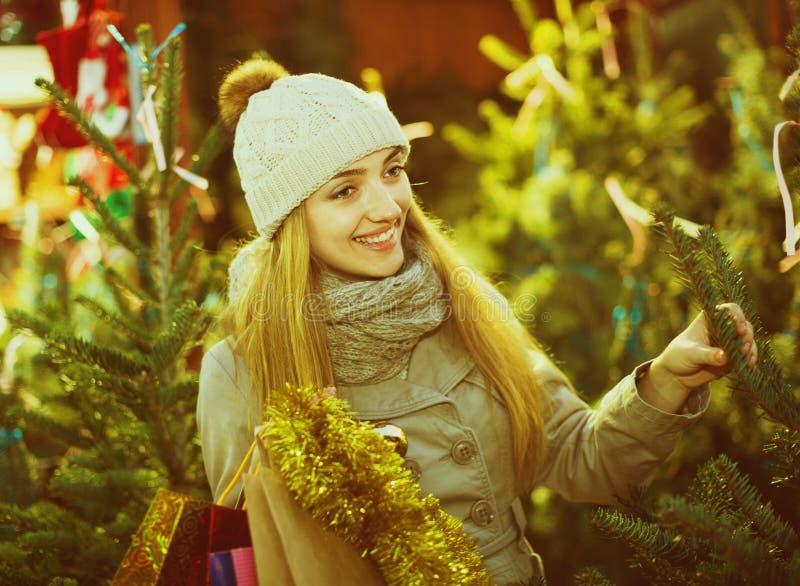 Jonge vrolijke vrouw het kopen Kerstmisboom bij feestelijke markt royalty-vrije stock afbeelding