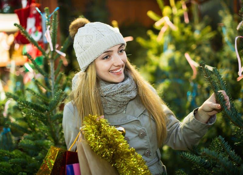 Jonge vrolijke vrouw het kopen Kerstmisboom bij feestelijke markt stock foto's