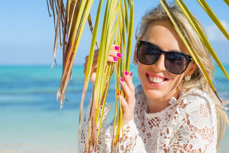 Jonge vrolijke vrouw op het strand die achter palmblad verbergen stock afbeelding