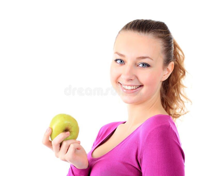 Jonge vrolijke vrouw in sportenslijtage met appel, die over wh wordt geïsoleerdo stock foto