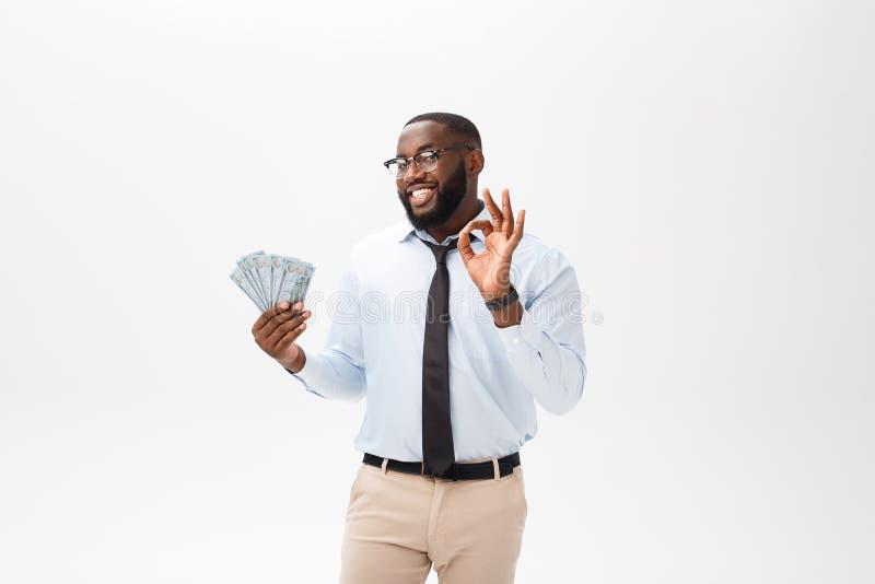 Jonge vrolijke zwarte die zakenmanholding en het richten op geld op wit wordt geïsoleerd stock foto's