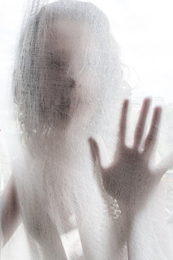 Jonge Vrouw achter een Wit Gordijn stock afbeelding