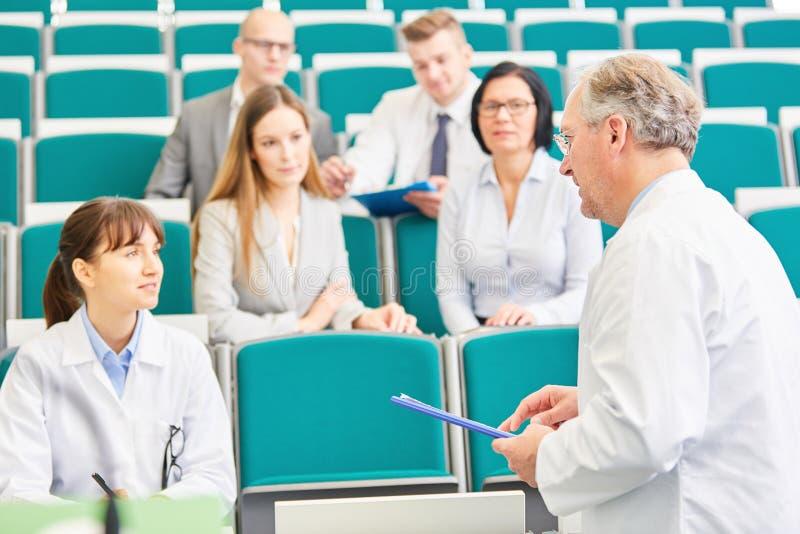 Jonge vrouw als geneeskundestudent in examen stock foto