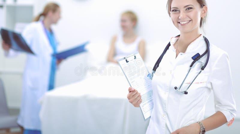 Jonge vrouw arts die zich bij het ziekenhuis met medische stethoscoop bevinden stock foto's