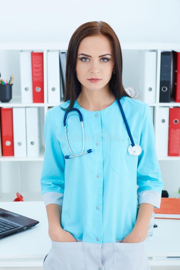 Jonge vrouw arts met blauwe laag die zich in het ziekenhuis bevinden Medisch hulp of verzekeringsconcept stock fotografie