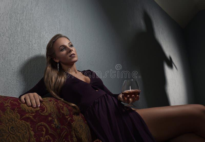 Jonge vrouw in avondjurk en de beklaagde` s schaduw op wal stock afbeeldingen