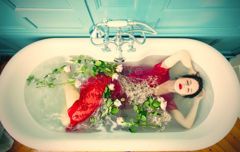 Jonge vrouw in bad met bloemen stock foto