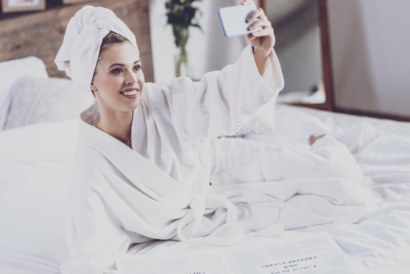 Jonge vrouw in badjas die fotograferen royalty-vrije stock foto's
