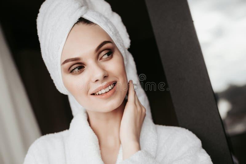 Jonge vrouw in badjas die zich op terras bevinden stock afbeeldingen