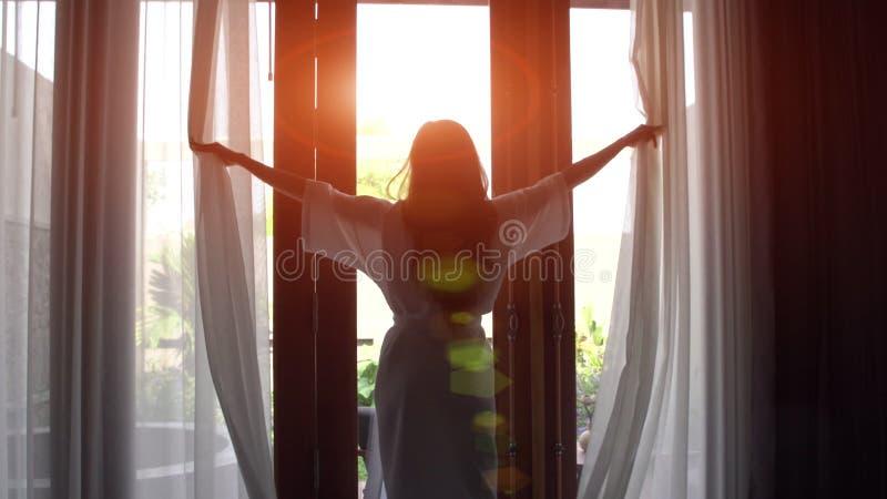 Jonge vrouw in badjas open gordijnen en rek die dichtbij het venster zich thuis bevinden royalty-vrije stock afbeelding