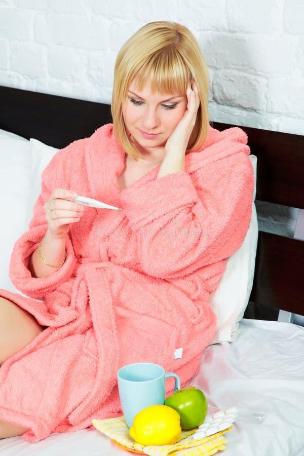 Jonge vrouw in bed dat griep heeft stock foto's