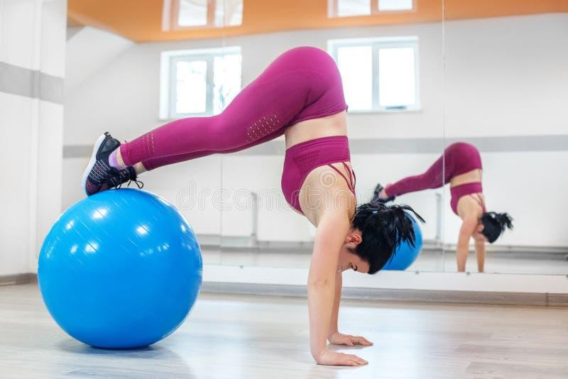 Jonge vrouw belast met machtsgeschiktheid in de gymnastiek Het concept sporten, een gezonde levensstijl, verliezend gewicht royalty-vrije stock afbeeldingen