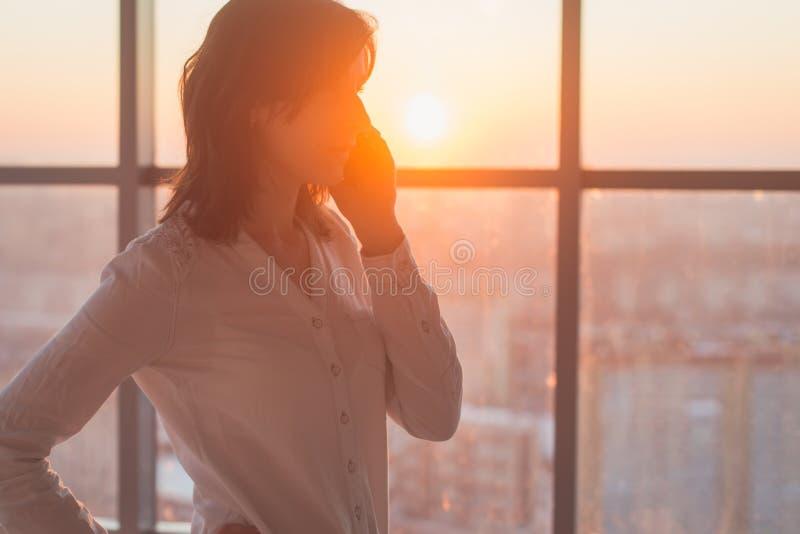 Jonge vrouw bezig met roepen, die op het het zijaanzichtportret van de celtelefoon babbelen Close-upbeeld van een onderneemster stock afbeelding