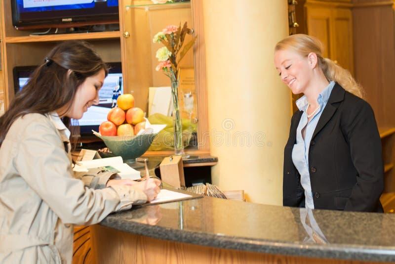 Jonge vrouw bij de hotelontvangst stock fotografie