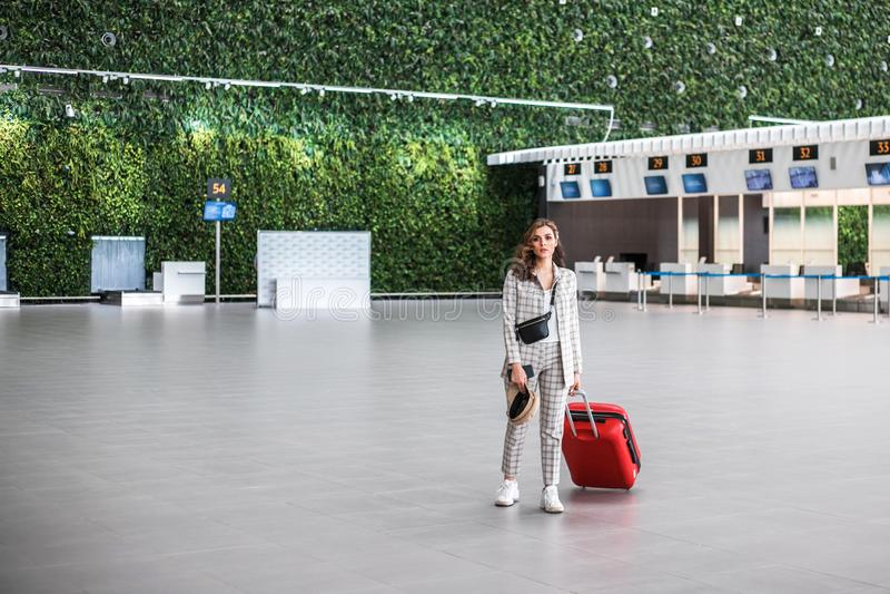 Jonge vrouw bij de luchthaven met koffer royalty-vrije stock afbeeldingen